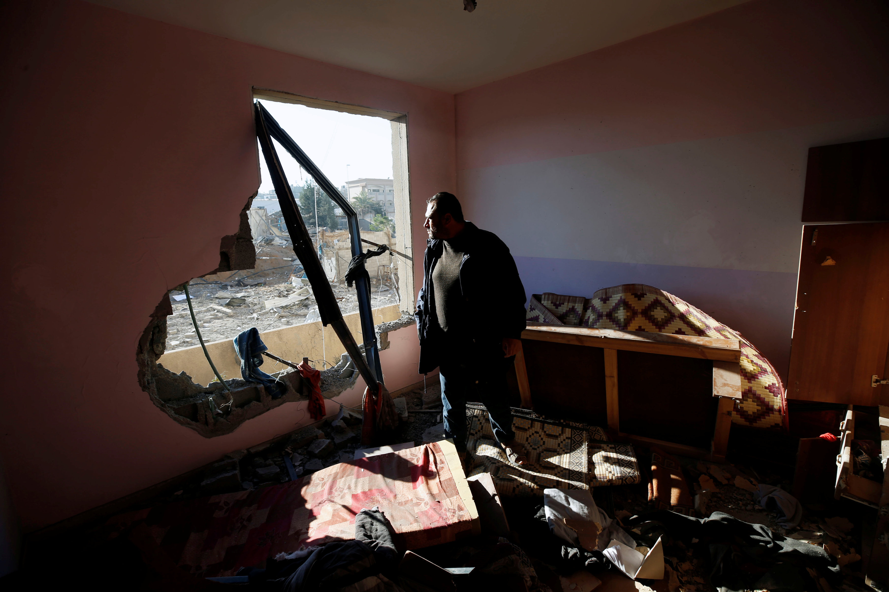 A Palestinian man looks out of his apartment that was damaged in an Israeli airstrike at a nearby militant target in the northern Gaza Strip December 9, 2017