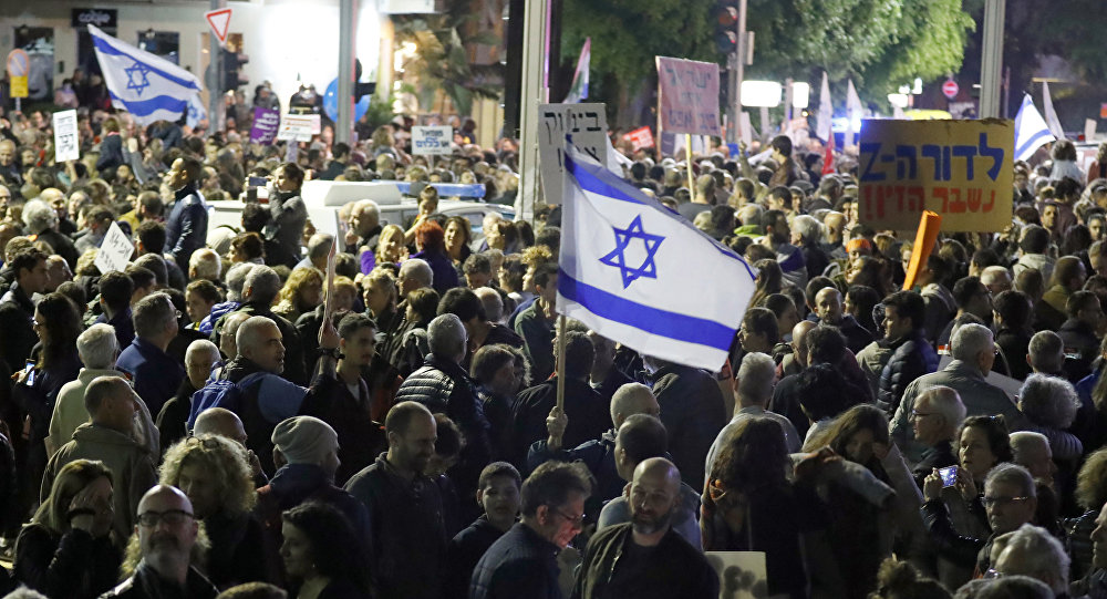 Israelis take part in a demonstration under the name March of Shame to protest against government corruption and Prime Minister Benjamin Netanyahu on December 9, 2017 in Tel Aviv