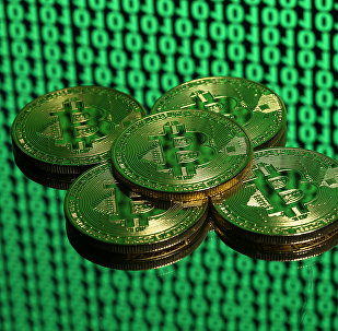 Tokens of the virtual currency Bitcoin are seen placed on a monitor that displays binary digits in this illustration picture, December 8, 2017