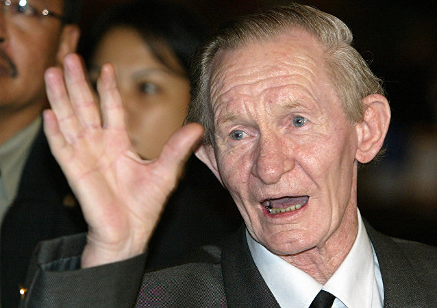 Former U.S. soldier Charles Robert Jenkins waves upon arriving at a Jakarta hotel from North Korea in this July 9, 2004 file photo
