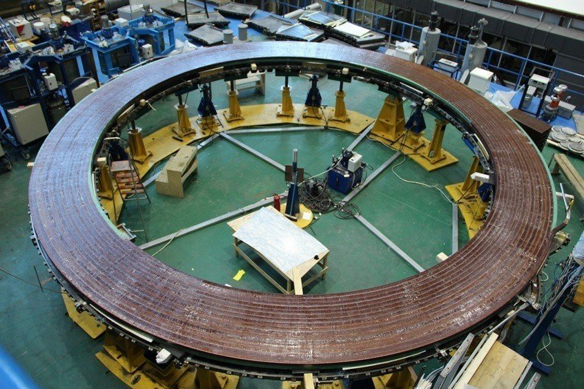 At the Srednenevsky Shipbuilding Plant in Saint Petersburg, Russia, specialists are winding the double pancakes for ITER's smallest poloidal field coil, PF1. Pictured is the first-completed double pancake after vacuum pressure impregnation with epoxy resin.