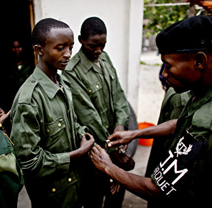 (File) A Congolese solider places handcuffs on Shumbushu Eric, a soldier accused of rape and crimes against humanity, outside his holding cell in the town of Baraka on Thursday, Feb. 17, 2011