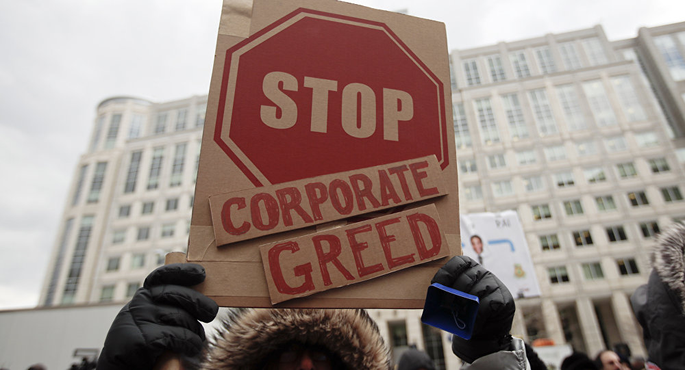 A woman hold a sign that reads Stop Corporate Greed during a protest at the Federal Communications Commission (FCC), in Washington, Thursday, Dec. 14, 2017