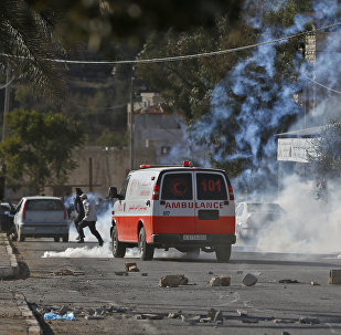 A Palestinian ambulance is seen driving amid teargas canisters shot by Israeli soldiers during clashed in the northern village of Qusra in the occupied West Bank near Nablus on December 4, 2017
