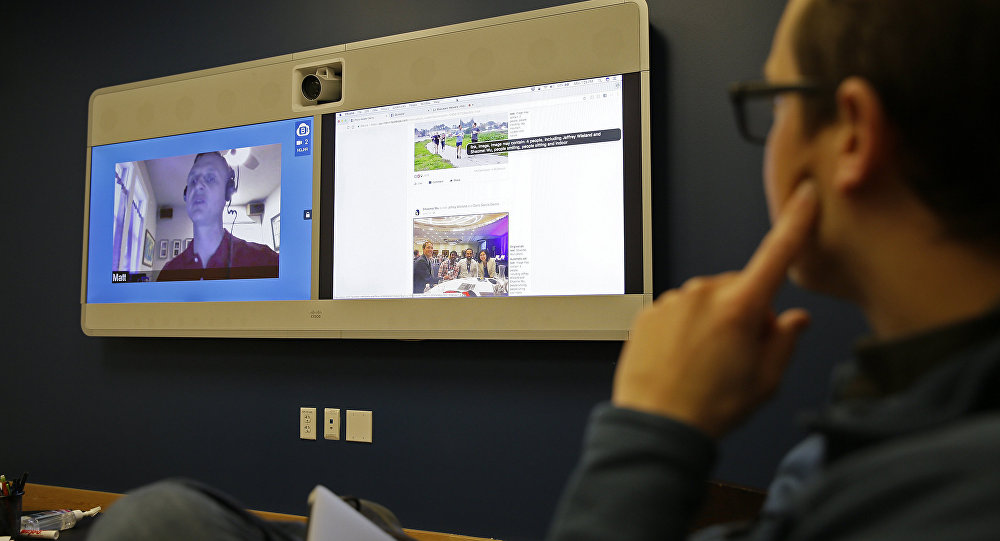 Jeff Wieland,, right, Facebook director of accessibility, watches as engineer Matt King, who is blind, demonstrates facial recognition technology via a teleconference at Facebook headquarters in Menlo Park, Calif