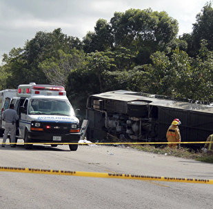 An ambulance sits parked next to an overturned bus in Mahahual, Quintana Roo state, Mexico