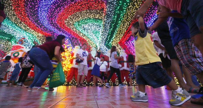 Filipinos pose as they tour the inside of the Christmas House owned by businessman Alexander Cruz in suburban Cainta, Rizal province east of Manila, Philippines