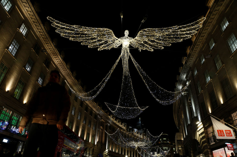 A man walks beneath Christmas street lights on Regent Street in London, Britain