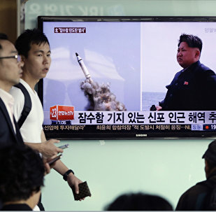 South Korean men pass by a TV news program showing images published in North Korea's Rodong Sinmun newspaper of North Korea's ballistic missile believed to have been launched from underwater and North Korean leader Kim Jong-un, at Seoul Railway station in Seoul, South Korea, Saturday, May 9, 2015