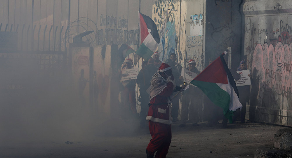 A Palestinian dressed as Santa Claus reacts from tear gas fired by Israeli troops during clashes in the West Bank city of Bethlehem, December 23, 2017