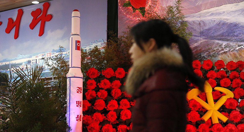 FILE - In this Feb. 15, 2016 file photo, a visitor at a flower festival walks past a model of North Korea's newest satellite Kwangmyongsong 4 on display