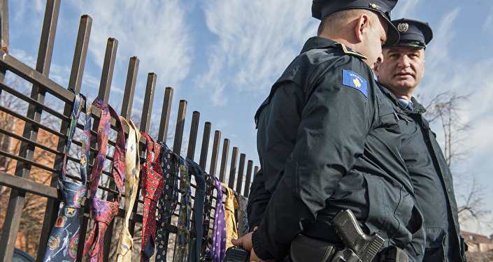 Kosovo police officers guard the entrance of prime ministers office as hundred of collected ties hung on the fence of the government building on Tuesday, Dec. 26, 2017, in Kosovo capital Pristina