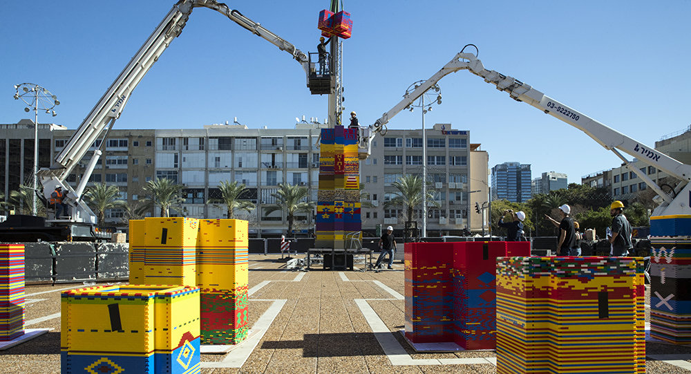 Workers and volunteers help assemble bricks during the construction of a LEGO tower in Tel Aviv's Rabin Square on December 26, 2017, as the city attempts to break Guinness world record of the highest such structure