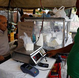 A vendor weighs cheese for a customer at a street market in Caracas, Venezuela December 19, 2017. Picture taken December 19, 2017.