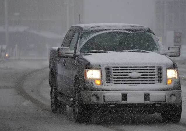 As a late winter storm envelops the region, a motorist guides his Ford F-150 pickup truck along a city street Wednesday, Feb. 25, 2015, in Denver