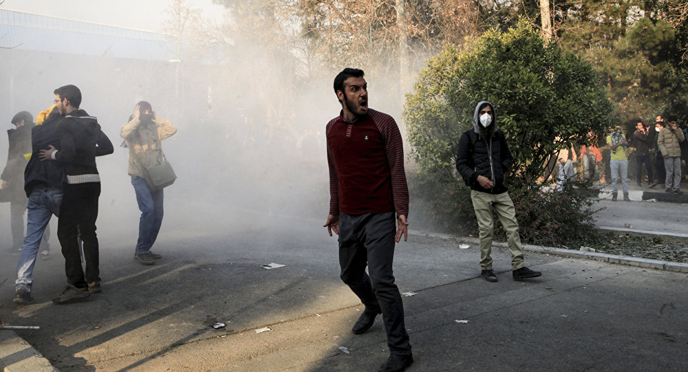 Iran, university students attend a protest inside Tehran University while a smoke grenade is thrown by anti-riot Iranian police, in Tehran, Iran, Saturday, Dec. 30, 2017