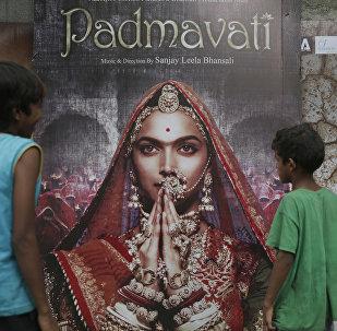 Boys look at a poster of Bollywood film 'Padmavati' in Mumbai, India, Tuesday, Nov. 21, 2017.