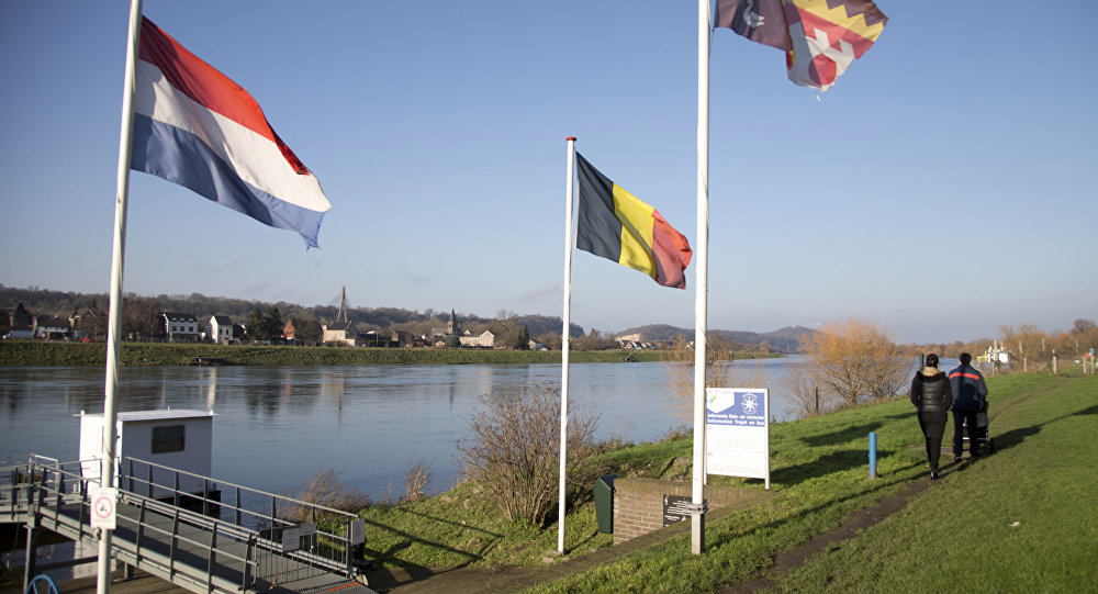 People walk past Dutch and Belgian flags on the waterfront in Eijsden, Netherlands (File)