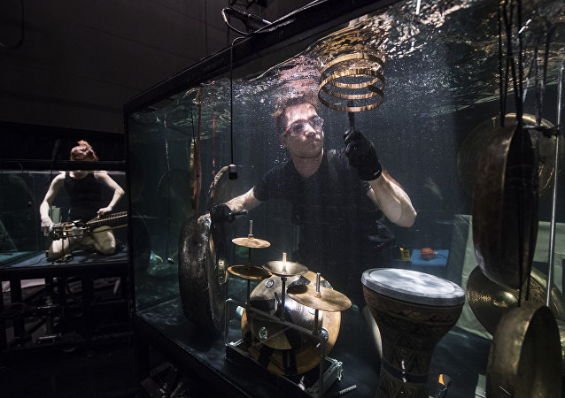 Members of the Between Music band, perform with custom-made instruments in a glass water tank during a rehearsal ahead of the AquaSonic underwater concert on April 19, 2017 in Aarhus, Denmark