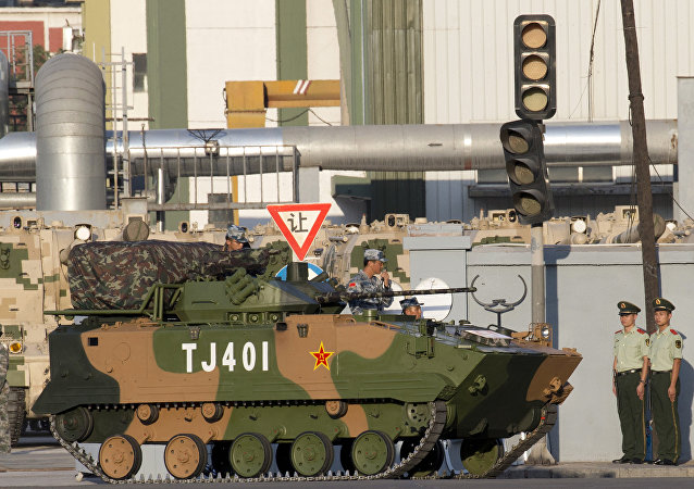 In this Aug. 22, 2015 file photo, a Chinese ZBD-03 airborne armored infantry fighting vehicle waits to take part in a rehearsal for a large military parade in Beijing. When China rolls out its latest armaments Thursday, Sept. 3