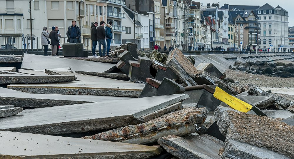 People look at the damaged seawall caused by the Storm Eleanor which swept through Europe, in Wimereux, northern France, on January 6, 2018