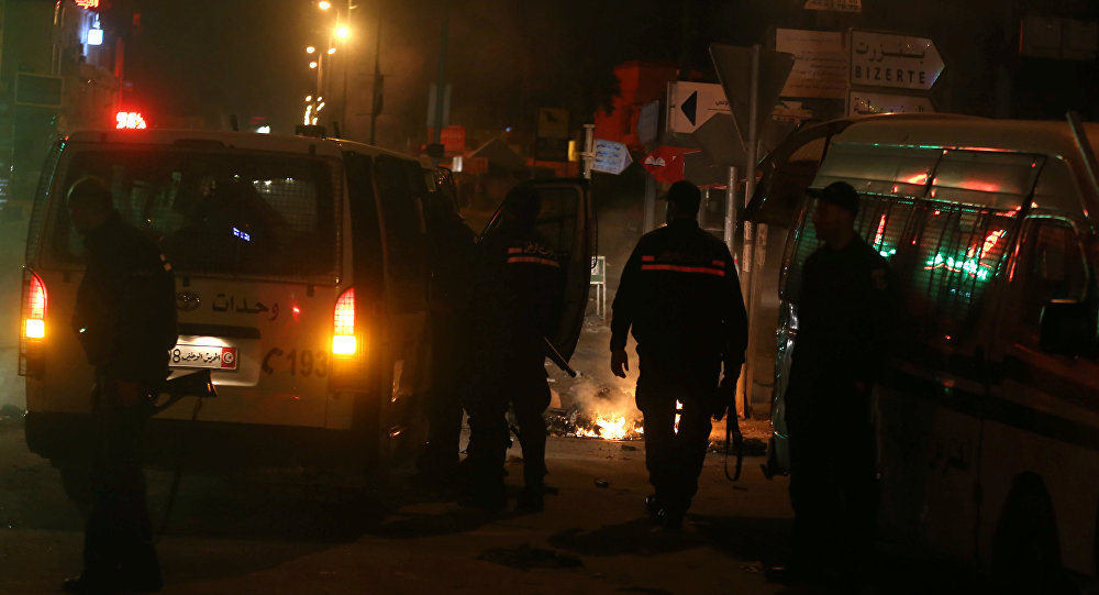 Police vehicles stop in front of burning tires set up by protesters during demonstrations against rising prices and tax increases in Tunis Tunisia