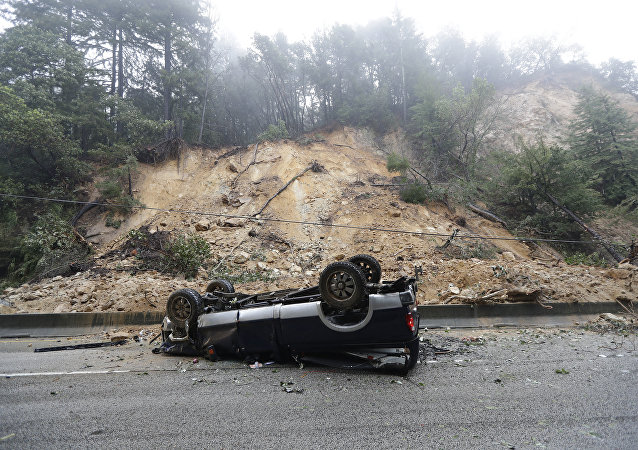 An overturned vehicle blocks a south bound lane next to a mudslide on Highway 17 Tuesday, Feb. 7, 2017, south of Santa Cruz, Calif.
