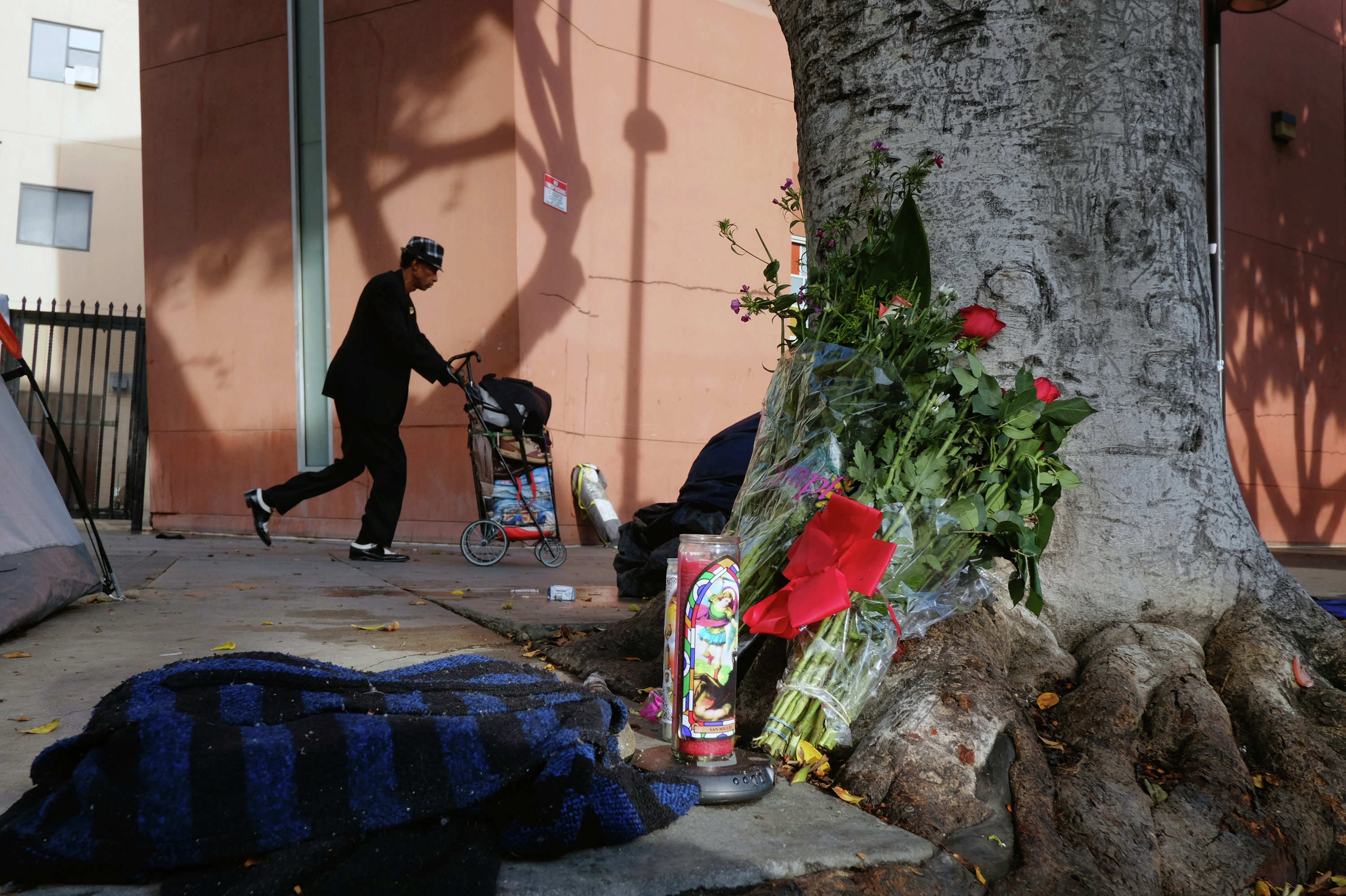 A pedestrian walks past flowers and candles placed on a sidewalk near where a man was shot and killed by police in the Skid Row section of downtown Los Angeles