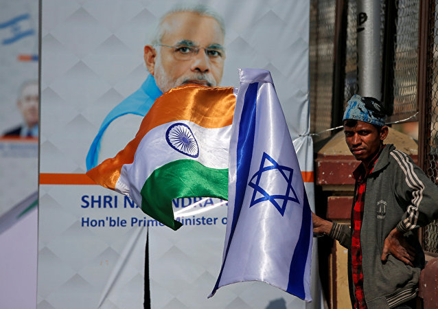 A man holds flags of India and Israel before installing them on a lamp post ahead of the visit of Israeli Prime Minister Benjamin Netanyahu in Ahmedabad, India January 15, 2018