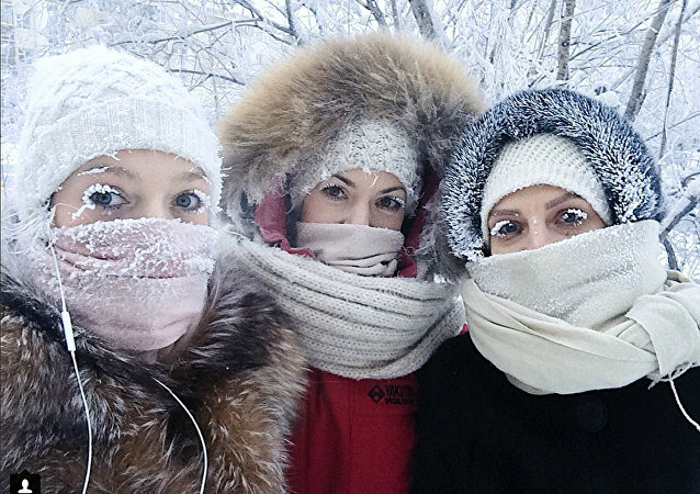 In this photo taken on Sunday, Jan. 14, 2018, Anastasia Gruzdeva, left, poses for selfie with her friends as the temperature dropped to about -50 degrees (-58 degrees Fahrenheit) in Yakutsk, Russia