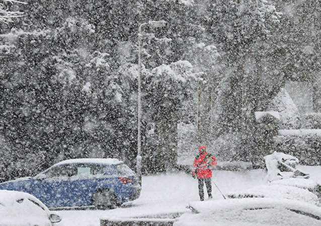 A postman delivers mail in snowy conditions in Braco in Perthshire, Scotland
