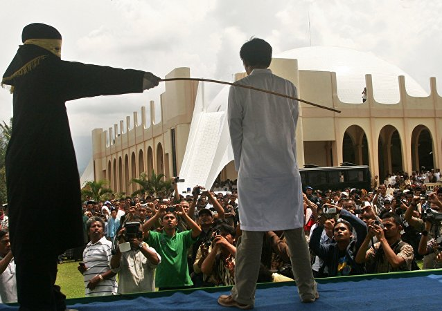 A Sharia law official whips a man , Aceh province, Indonesia (File)