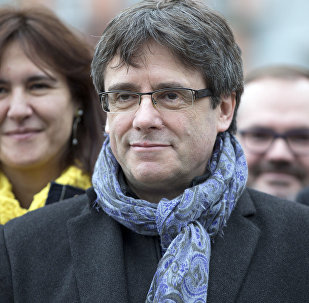 Ousted Catalan leader Carles Puigdemont, center, stands with elected Catalan lawmakers of his Together for Catalonia party at a park in Brussels