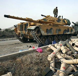 Turkish Army soldiers prepare their tanks next to empty shells at a staging area in the outskirts of the village of Sugedigi, Turkey, on the border with Syria, Monday, Jan. 22, 2018