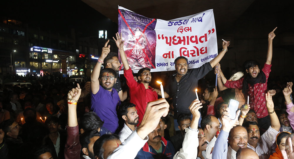 Members of India's Rajput community holds a banner and candles and shouts slogans during a protest against the release of Bollywood film Padmaavat in Ahmadabad, India