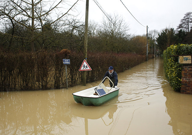 A resident pushes a dinghy boat in a flooded street of Esbly, east of Paris, where the Grand Morin river floods
