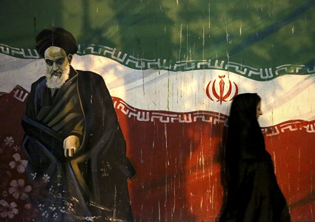 veiled Iranian woman walks past a mural depicting the late revolutionary founder Ayatollah Khomeini, and national Iranian flag, painted on the wall of the former U.S. Embassy, in Tehran, Iran