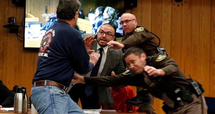 Randall Margraves (L) lunges at Larry Nassar (wearing orange) a former team USA Gymnastics doctor who pleaded guilty in November 2017 to sexual assault charges, during victim statements of his sentencing in the Eaton County Circuit Court in Charlotte, Michigan