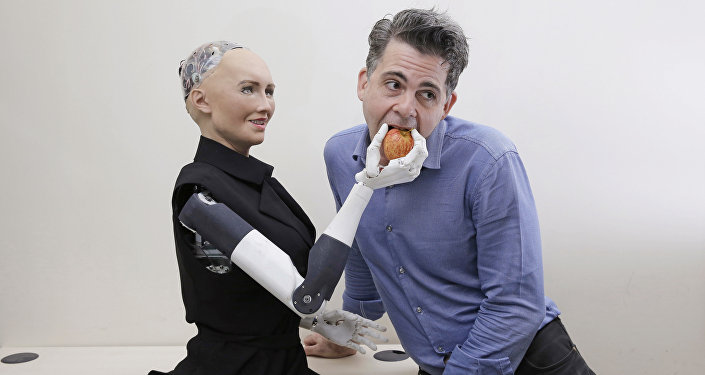 In this Sept. 28, 2017, photo, David Hanson, the founder of Hanson Robotics, poses with his company's flagship robot Sophia, a lifelike robot powered by artificial intelligence in Hong Kong