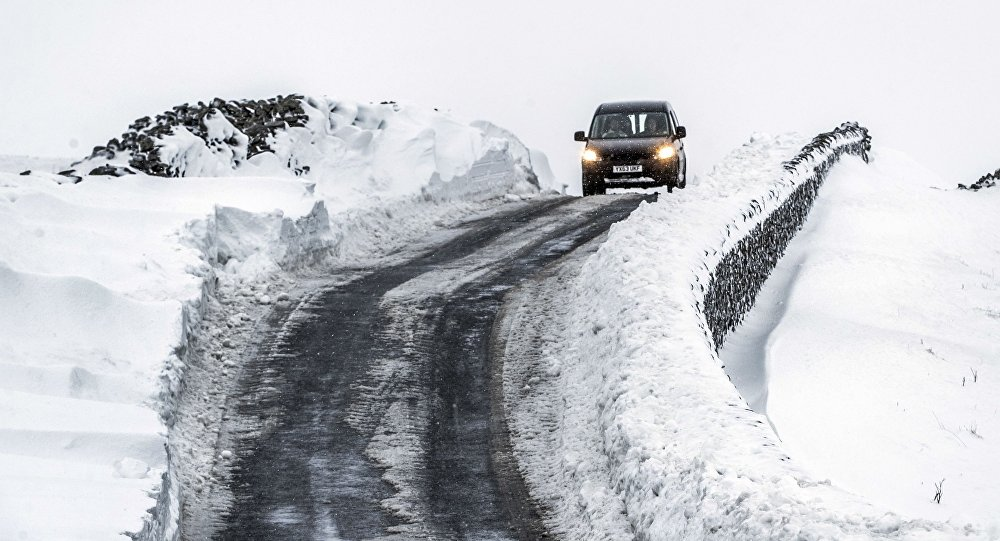 A vehicle drives in snowy conditions near Fleet Moss in the Yorkshire Dales National Park, north Engand, Sunday Jan. 21, 2018