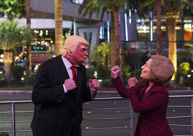 Donald Trump impersonator Rafael Almodovar, left, and Hillary Clinton impersonator Corina Almodovar entertain a crowd as early election results come in from a television display above, Tuesday, Nov. 8, 2016, during election night in Las Vegas