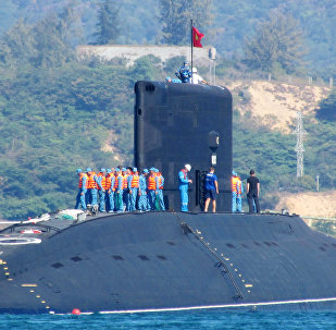 This picture taken on January 3, 2014 shows the Vietnamese Navy's first submarine class Kilo 636 (C) named 'Hanoi' being released into the sea from a Netherland's transporting ship Rolldock Sea at Cam Ranh Bay in central Vietnam