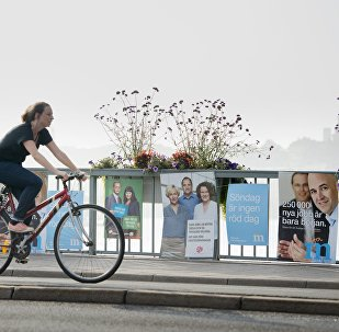 A girl on a bicycle passes general election posters for the Social Democrats party and the Moderaterna conservative party (right) in central Stockholm, Friday Sept. 12, 2014 (photo used for illustration purpose)