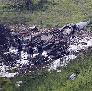 Israeli security stands around the wreckage of an F-16 that crashed in northern Israel, near kibbutz of Harduf, Saturday, Feb. 10, 2018.