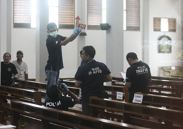 In this image shot through a glass window, police investigators examine the interior of St. Lidwina Church following an attack in Sleman, Yogyakarta province, Indonesia, Sunday, Feb. 11, 2018.