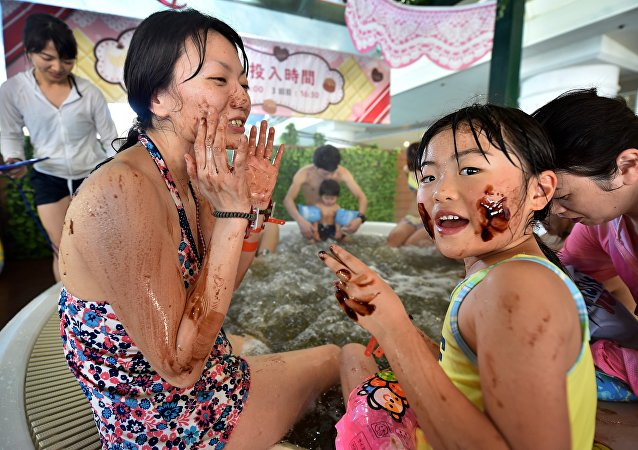 A woman and her daughter put chocolate on their faces as they bath in a 'chocolate spa' at the Hakone Yunessun spa resort facilities in Hakone, Kanagawa prefecture