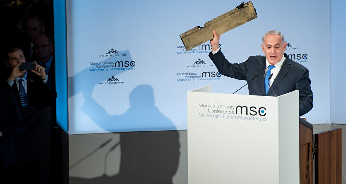 Israeli Prime Minister Benjamin Netanyahu holds up a remnant of what he said was a piece of Iranian drone which was shot down in Israeli airspace during his speech at the Munich Security Conference, Germany February 18, 2018