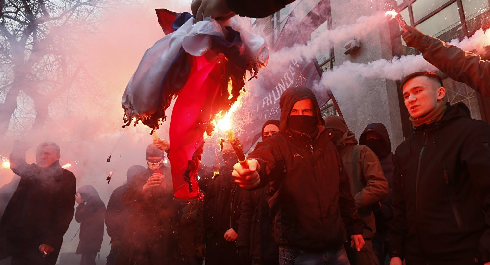 Activists and supporters of Ukrainian nationalist parties and movements burn the Russian state flag, which was seized from the office of the Russian Centre of Science and Culture, during a protest in Kiev, Ukraine February 17, 2018