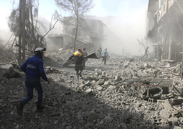 Members of the Syrian Civil Defense run to help survivors from a street that attacked by airstrikes and shelling of the Syrian government forces, in Ghouta, suburb of Damascus, Syria
