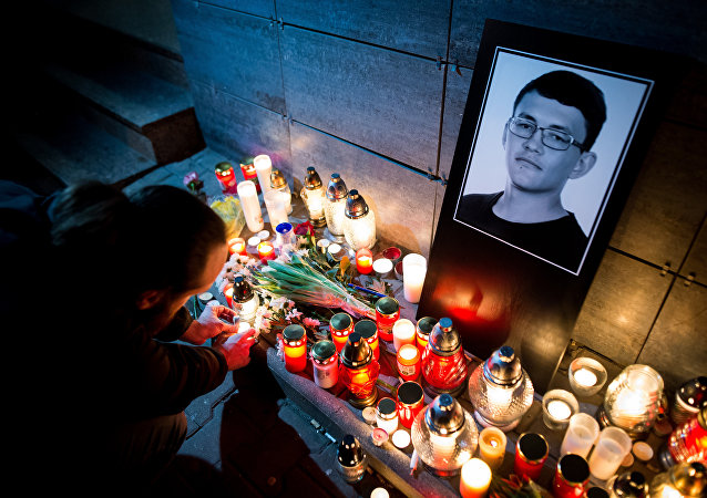 A man lits a candle in front of the Aktuality newsroom, the employer of the murdered investigative journalist Jan Kuciak, on February 26, 2018 in Bratislava
